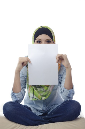 Beautiful young muslim woman seat and holding a blank paper.half face covered by blank paper photo