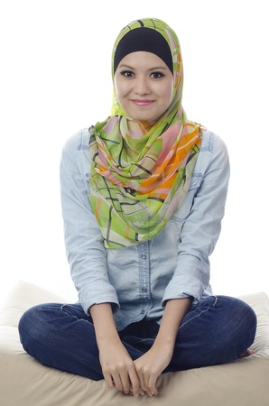 beautiful muslim woman with stylish head scarf smiling and sitting cross-legged on a couch