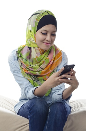 beautiful young muslim woman with colorful head scarf sending text messaging photo