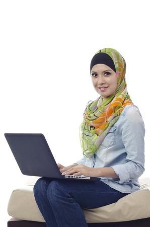 Mooie moslim vrouw glimlachend met laptop op haar rondjes