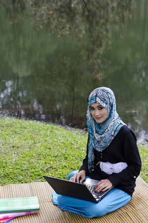 beautiful young muslimah woman with head scarf happy using laptop near lake Фото со стока