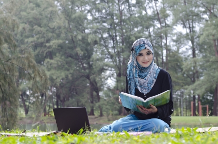 beautiful young muslimah woman with head scarf relax while reading a book at the recreation park photo