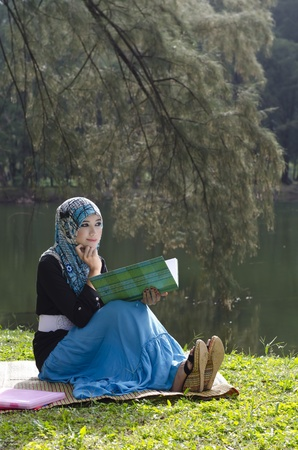 malay ethnicity: beautiful young muslimah woman with head scarf thinking while reading a book near the lake Stock Photo