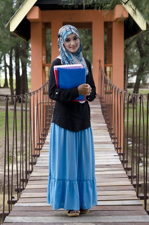malay ethnicity: beautiful young muslimah woman with head scarf holding the books and standing on hanging bridge at recreation park