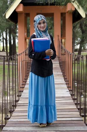 mooie jonge moslima vrouw met hoofddoek die de boeken en staande op de opknoping brug bij recreatiepark