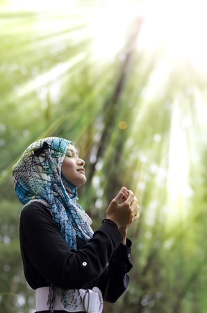 beautiful young muslimah woman with head scarf standing and praying under rays of light photo