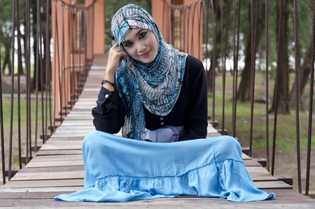 beautiful young muslimah women with stylish head scarf sit on the hanging bridge at recreation park photo