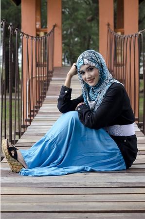 mooie jonge moslima vrouwen met een stijlvolle hoofddoek lachend zitten op de opknoping brug bij recreatiepark Stockfoto