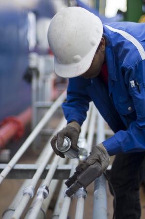 werknemer met persoonlijke beschermingsmiddelen uit te voeren Magnetic Particle Inspection 'MPI' op lasnaad pijplijn Stockfoto