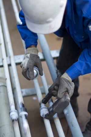 werknemer met persoonlijke beschermingsmiddelen het controleren van de kwaliteit van de lasnaad met behulp van Magnetic Particle Inspection