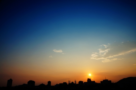 silhouette of urban skyline isolated on orange sunset and blue sky view
