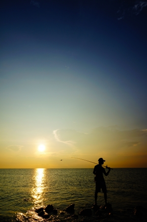 silhouette of people standing on the rocks while fishing isolated over sunrise and dramatic sky photo