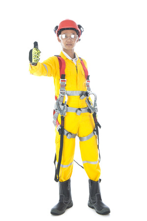 A man complete with personal protective equipment wearing safetyl body harness showing thumb up Stock Photo