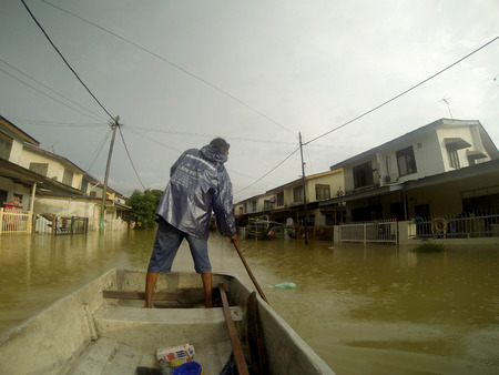 KUANTAN, PAHANG MALAYSIA-DEC 05:Unidentified boy is rowing a boat to enter his hometown after strucked by the largest t floods in history