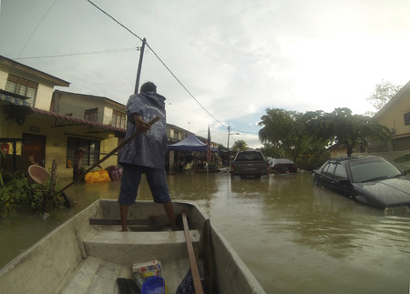 KUANTAN ,PAHANG MALAYSIA-DEC 05:Unidentified boy trying to enter his home and stucked by vehicle submerged by the largest floods in history