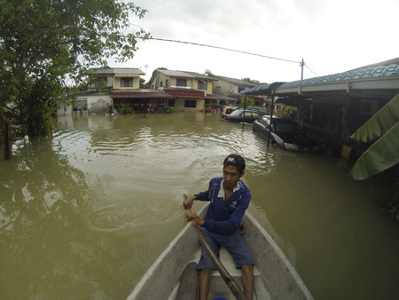 KUANTAN, PAHANG, MALAYSIA-DEC 05:Unidentified boy is rowing a boat to enter his home after strucked by the worst floods in the history