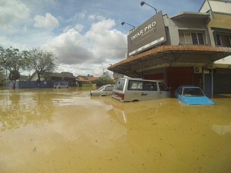 the worst: KUANTAN, PAHANG MALAYSIA-DEC 05:Unidentified tires shop and a few of vehicles submerged after strucked by the worst floods in history Editorial