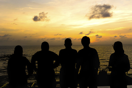 helideck: Silhouette of offshore workers standing on helipad during sunset with ocean background.