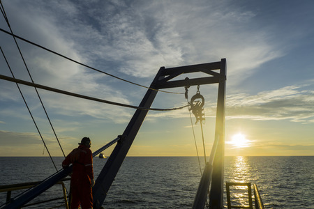 subsea: Worker standing on the platform waiting for arrival robotics Remote Operated Vehicle (ROV) for the sea during sunrise. Stock Photo