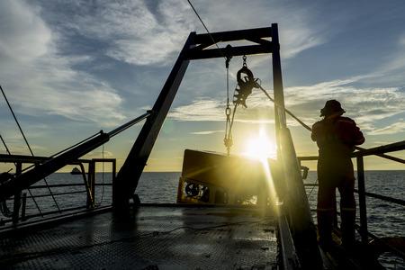 Silhouet van de werknemer herstellen van robotica Remote Operated Vehicle (ROV) na het invoeren van het zeeoppervlak in de olie- en gaspijpleiding inspectie in het midden van de Zuid-Chinese Zee die op zonsopgang met verblinding.