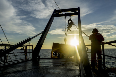 Silhouette of worker recovering robotics Remote Operated Vehicle (ROV) after entering sea surface during oil and gas pipeline inspection in the middle of South China Sea isolated on sunrise with glare.