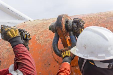 crew: Marine crew doing anchor handling activities with selective focus.