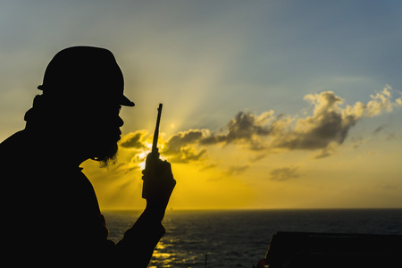 walkie talkie: Silhouete people of offshore crew holding walkie talkie isolated with sunrise view