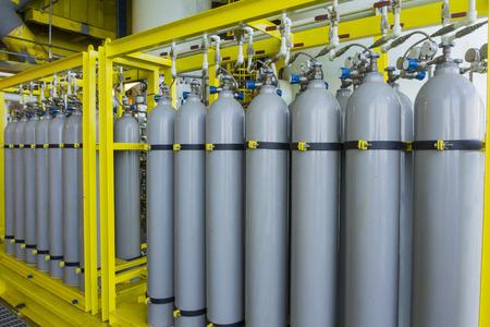 Ein Bündel von grauen Gasflaschen gesichert auf gelbem Skids in der Öl- und Gas rig Plattform. Standard-Bild