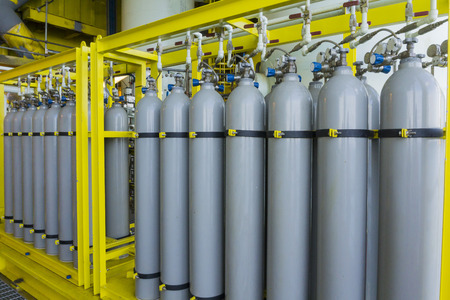A bundle of grey gas cylinders secured on yellow skids in oil and gas rig platform. Banque d'images