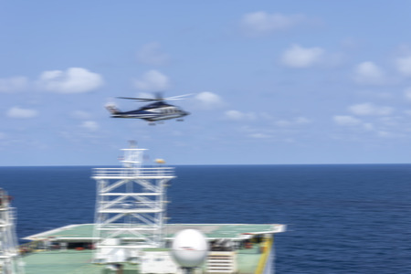 helideck: Motion blur effect. Helicopter landing on barge helideck, Helicopter transfer crews or passenger to work in offshore oil and gas industry, air transportation for support passenger, ground service in airport. Stock Photo