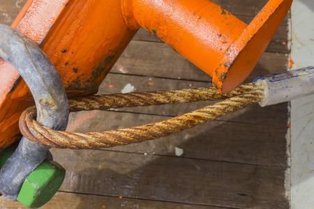 heavy weight: Industrial equipment. A heavy weight shackle with rusty wire ropes attached to pad eye buoyancy tank for anchor handling activities. Stock Photo