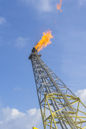Flare boom nozzle and fire on offshore oil and gas rig platform with blue sky.