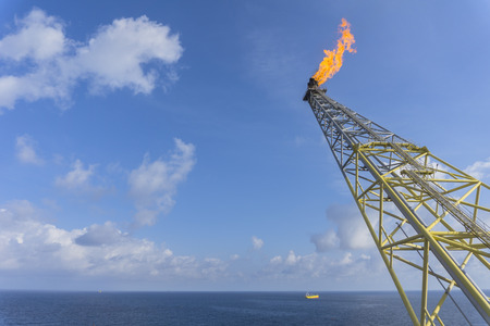 Offshore works. Flare boom nozzle and fire on offshore oil and gas rig platform with oil tanker process and blue sky in the middle of the ocean.