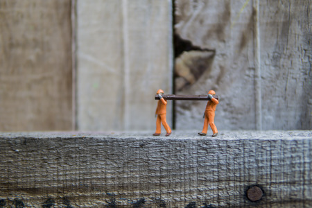 Miniature figures working in industrial - Close up of construction worker doing manual handling together concept with selective focus.