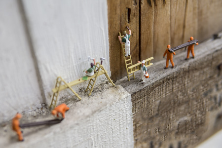 Miniature figures working in industrial - Close up of construction and painting workers concept with selective focus.