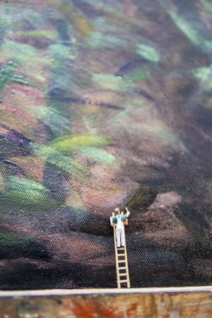 Miniature figures painting - painter in action concept