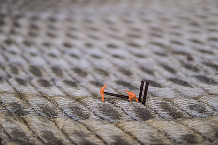 Miniature figure working in industrial - Close up of construction workers teamwork concept on rope surface with selective focus. Stock Photo
