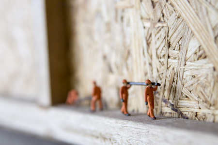 Miniature figure working in industrial sector - Close up of construction workers teamwork concept with selective focus.