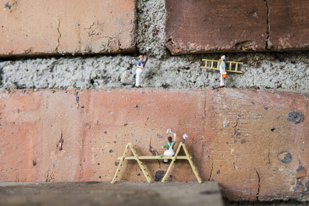 Miniature figure working in industrial sector - Close up of cleaning and painting workers teamwork concept with selective focus.
