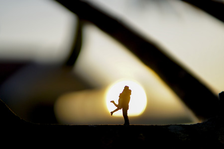 Loving couple concept - Silhouette of loving couple hugging from miniature action figure with background sunset.