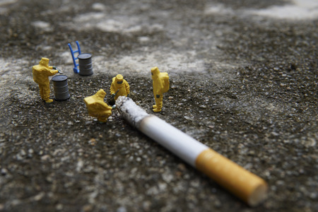 Miniature figures working in industrial - Close up of Hazardous Material (HAZMAT) teamwork concept with half cigarette on the floor.