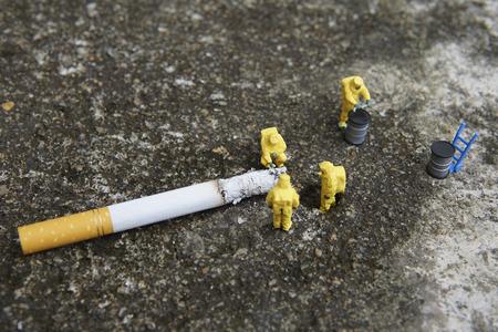 Miniature figures working in industrial - Close up of Hazardous Material (HAZMAT) teamwork concept with half cigarette on the floor.