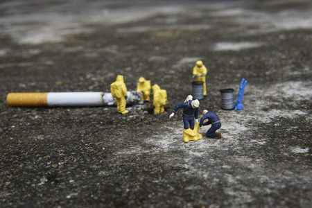 Miniature figures working in industrial - Close up of Hazardous Material (HAZMAT) personnel helping his colleague wearing protective clothing with background half cigarette on the floor.