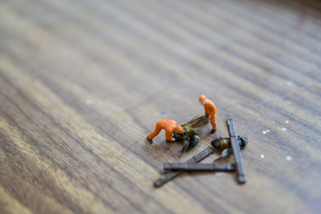 Miniature figure accident in workplace - Close up of construction workers try to lift up dead hornet accident concept with selective focus.