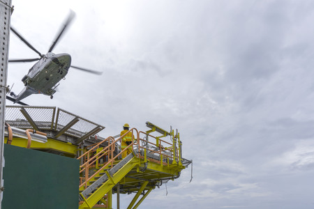 Aviation transportation. A commercial helicopter take off from oil and gas helideck during cloudy and raining slightly while fire fighter with yellow fire suit watching the situation.