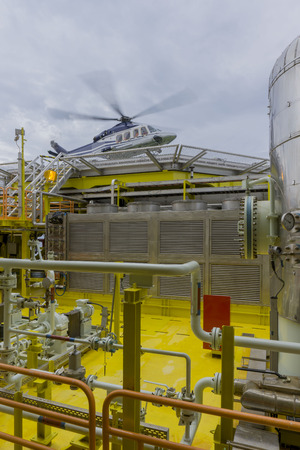Oil and gas industry. View from process area on oil and gas platform with commercial helicopter landing on helideck.