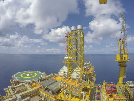 Oil and gas industry. Aerial view process area of oil and gas platform with many facilities, helicopter landing deck and pedestal crane with blue sky. Stock Photo