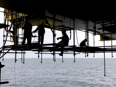 Oil and gas industry. Silhouette of offshore workers with fall protection device working overboard below oil and gas platform in the middle of the sea.