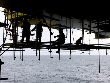 Industrie du pétrole et du gaz. Silhouette de travailleurs offshore avec dispositif de protection contre les chutes travaillant par-dessus bord au-dessous de la plate-forme pétrolière et gazière au milieu de la mer.