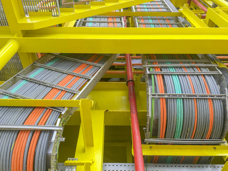 Oil and gas industry. High voltage electrical cables layout on cable tray and yellow steel structure at oil and gas platform. Stockfoto